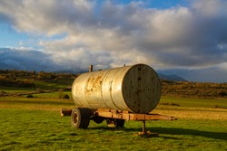 A scenic view of a natural landscape with an old rusty water cannon trailer