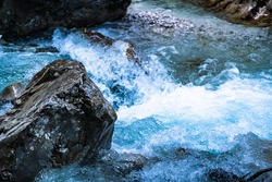 A scenic view of a river with clear blue water flowing among boulders and between rock cliffs