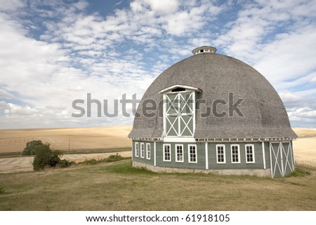 A scenic view of a round barn with a blue sky in the background.