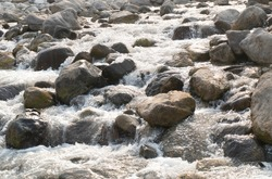 A scenic view of flowing water running downstream over big rocks