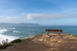 A scenic viewpoint with wooden bench on beautiful ocean coast with high cliffs and big waves