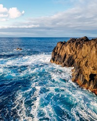 A scenic waterscape with waves crashing against the cliffs on Sao Miguel Island, Azores