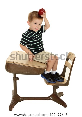 A school boy sits on a desk holding an apple on his head isolated on white