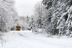 A school bus drives down a snow covered rural country road lined with snow covered trees after a snow storm during the winter season.