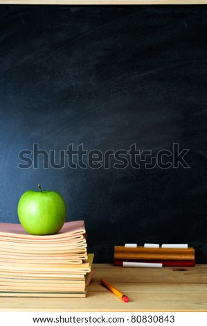 A school chalkboard and teacher\'s desk with stack of exercise books and an apple. Copy space on blackboard.  Portrait (vertical) orientation.