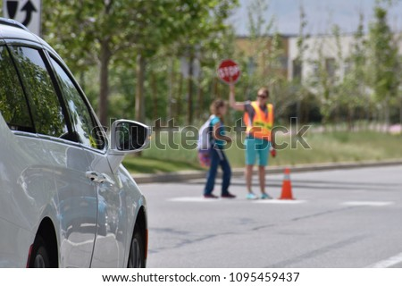 A school crossing guard walks a student across a crosswalk holding a STOP sign #1095459437