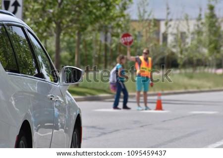 A school crossing guard walks a student across a crosswalk holding a STOP sign