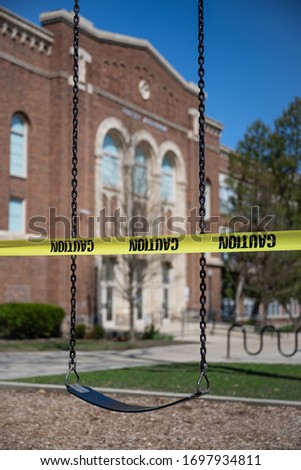 A school playground in Michigan is sealed off with cordon tape. The State closed all schools to thwart the spread of the novel coronavirus. Foto stock ©