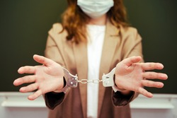 A school teacher in a medical mask with handcuffs, concept of captivity during the quarantine flu. Concept of problems at school during the coronavirus epidemic