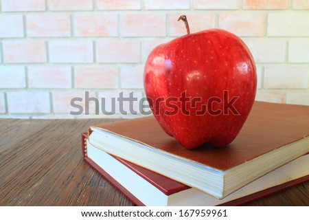 A school teacher\'s desk with stack of exercise books and apple . A blank blackboard in soft focus background provides copy space.