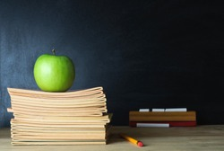 A school teacher's desk with stack of exercise books and apple in left frame. A blank blackboard in soft focus background provides copy space.