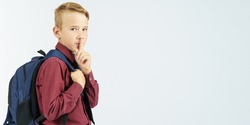 A schoolboy holds a school backpack and shows a gesture with his hand - be quiet. Education concept