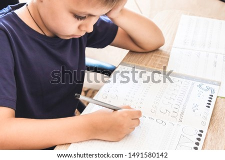 A schoolboy learns to write in a notebook. Pencil in the hands of children. The boy writes.