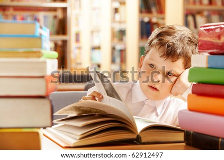 A schoolboy sitting in the library and turning the pages over