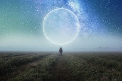 A science fiction concept. A man standing in a field looking out across space with a glowing portal in the night sky