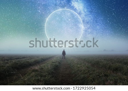 Photo of  A science fiction concept. A man standing in a field looking out across space with a glowing portal in the night sky