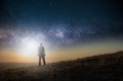 A science fiction concept. A man standing on a hill lookin gout across space with a bright light in the sky.