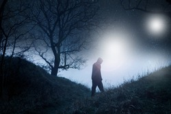 A science fiction concept of a spooky hooded figure in a wood in winter at night, silhouetted against stars and mysterious lights in the sky