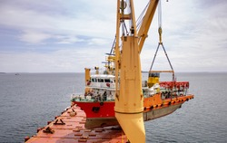 a scientific ship is loaded onto a deck of a heavy lift vessel  by tandem of two cranes with a pontoon installed