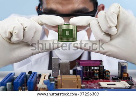 A scientist checking the computer chip of a motherboard