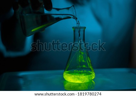 A scientist experimenting with a green fluorescent solution in a glass conical flask in dark biomedical laboratory for health care development