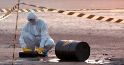 A scientist in a protective suit works in a biological contamination zone.