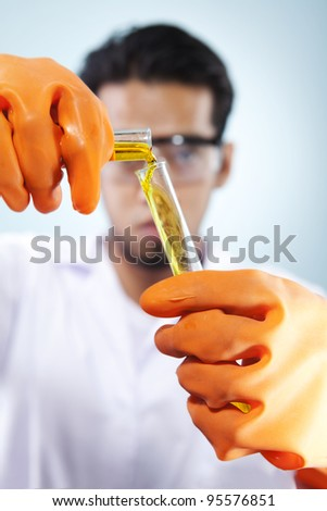 A scientist pouring the liquid chemical to his research in the laboratory research
