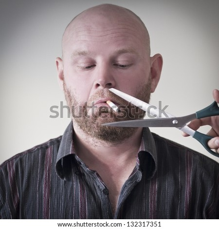 A scissors cuts the cigarette to a smoking man. Trying to quit smoking?
