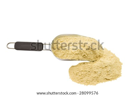 A scoop of nutritional yeast flakes isolated on a white background.