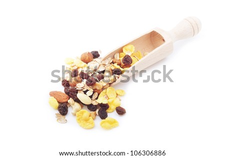 A scoop with mix of cereal, nuts and dried fruits