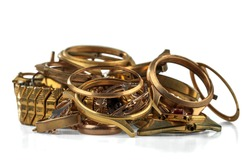 A scrap of gold. Old and broken jewelry, watches of gold and gold-plated isolated on a white background.
