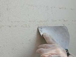A scraper in hands of a painter being used to remove sticky rough glue and tape remain on the old concrete wall, as a preparation before starting the paint the house