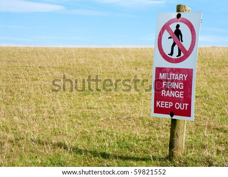 A scratched and worn red and white keep out sign on a wooden post in a field of green grass with blue sky.  Focus on the sign.