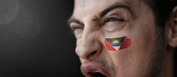 A screaming man with the image of the Antigua and Barbuda national flag on his face.