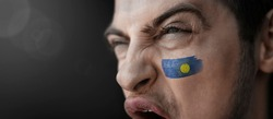 A screaming man with the image of the Commonwealth national flag on his face.