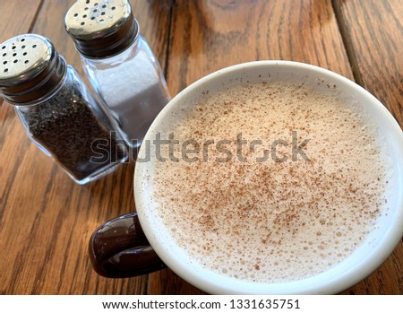 A scrumptious and foamy chai latte with cinnamon sprinkled on top from a gourmet coffee shop.