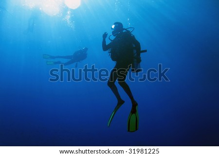 A scuba diver decompressing after dive. Surrounding waters are serene and penetrated by sun beams.