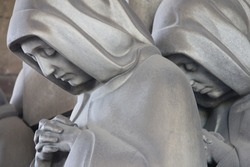 A sculpture of a group of sad women praying at the Monumental Cemetery in Milan, Italy