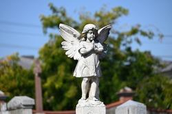 A sculpture of a praying cherub in a cemetery