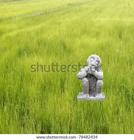 A sculpture of a stone monkey praying at the edge of a fertile rice field plantation.