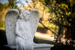 A sculpture of an angel in the autumn park.
