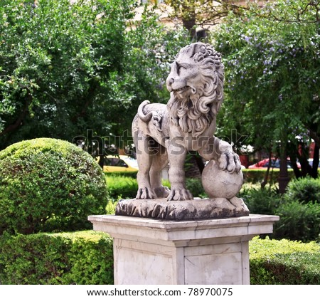A sculpture of lion in Seville park