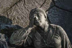 A sculpture of sad woman in grief. Virgin Mary stone statue (suffering, death concept)