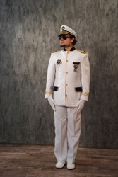 A sea captain in white uniform and sunglasses stands exactly at full height, turning his head to the side, isolated on a white background. Sea. A cruise ship.
