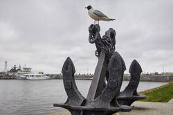 a seagull sits at anchor in the background of the seaport. pier with a lighthouse. gray cloudy sky.