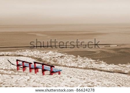 a seasonal snow covered view of atlantic ocean and bally bunion beach with red benches on a frosty snow covered winters day in sepia
