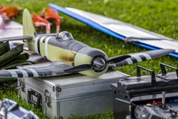 A second world war remote controlled warplane is lying on an aluminum case with some other accessories around