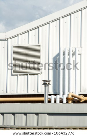 A section of an industrial unit with vent panel and a variety of piping.