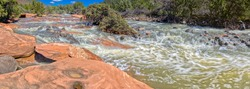 A section of Dry Beaver Creek south of Sedona AZ with red sandstone boulders and rapidly flowing water. Located in Woods Canyon.