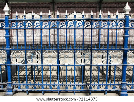 A section of royal blue cast iron fencing decorated with ornate silver circles and spikes at Darlington Railway Station, England.